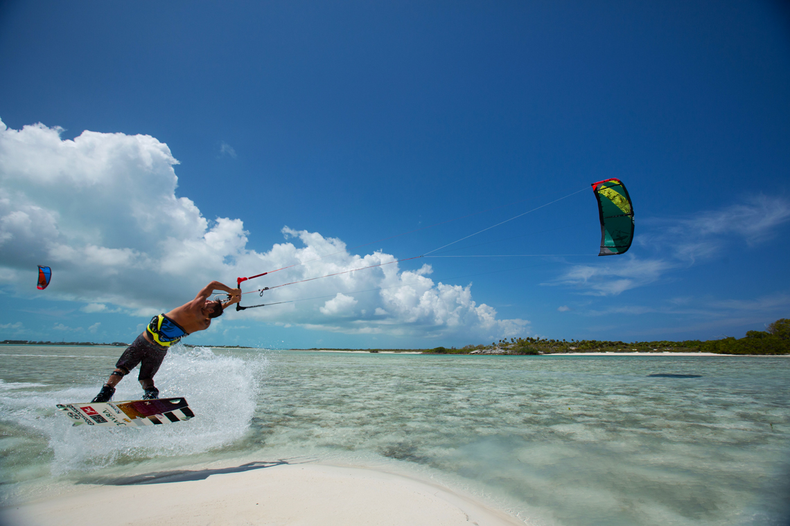 Kiteboarder Youri Zoon popping a jump over a tropical sandbar on his Best Kiteboarding gear.