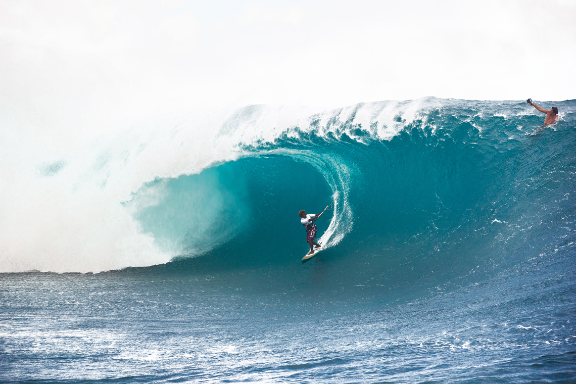 Mitu Monteiro on a huge day at Teahupoo, surfing wave, taking time for camera