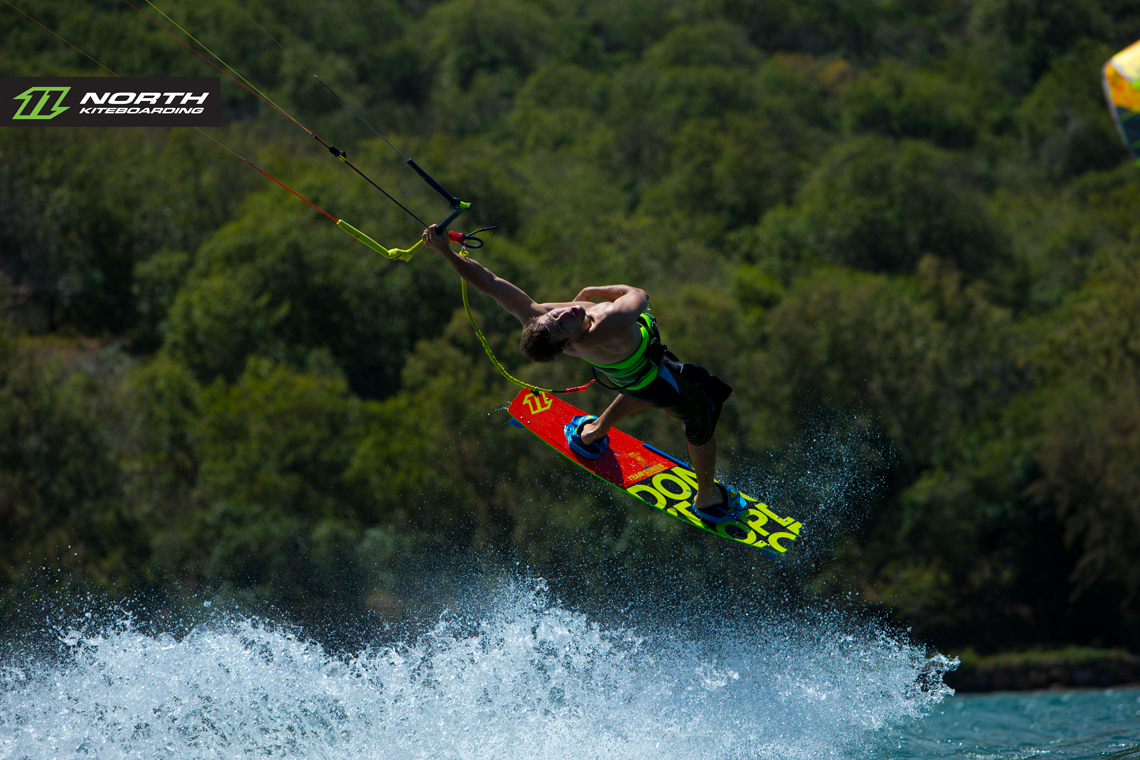 Tom Hebert swinging on one arm and riding the 2015 North Team Series - North kiteboarding
