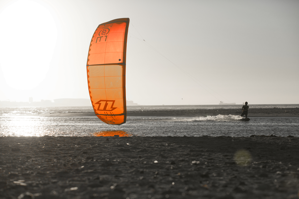 A kitesurfer cruising on the 2015 North kiteboarding Juice kite around sunset in light winds.
