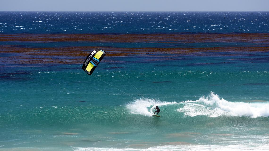 The 2016 Slingshot kiteboarding Wave SST kitesurf kite. Kitesurfer off the lip turn.