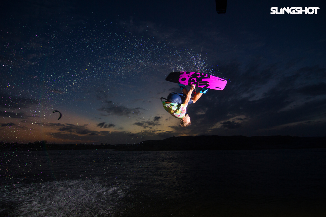 Sam Light on the 2015 Slingshot asylum board. Inverted with a grab kitesurfing.