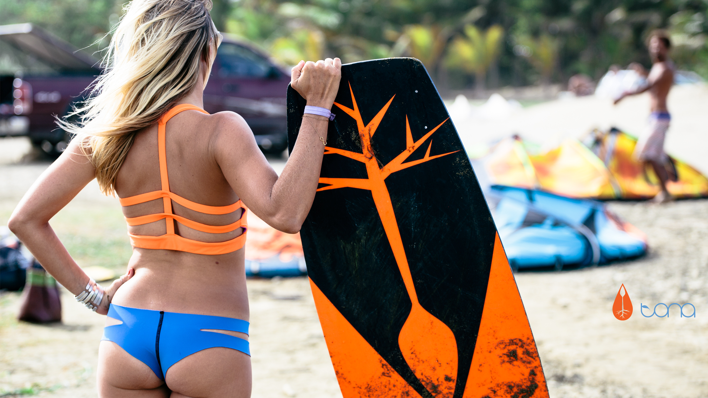 kitesurf wallpaper image - Susi Mai getting into the flow of Tona Boards posing with kiteboard - in resolution: High Definition - HD 16:9 2400 X 1350