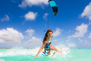 Speed queen Charlotte Consorti enjoying the tropics - kitesurfing in a blue and white bikini