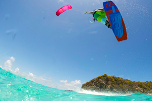 The 2016 North Kiteboarding Rebel kite and Gambler board over tropical waters. Kiteboarder jumping while girl dives under water.