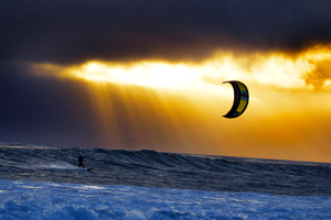 A kitesurfer cruising at sunset with his 2016 Slingshot Wave SST kite.