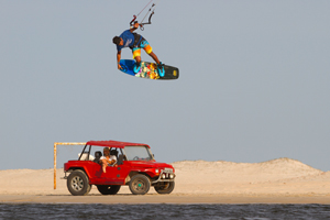 Victor Hays with a tail grab over a Brazilian buggy - Slingshot kiteboarding